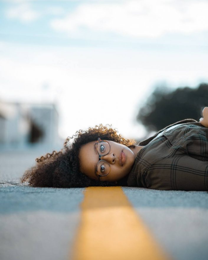 Portrait of woman lying on road stripe