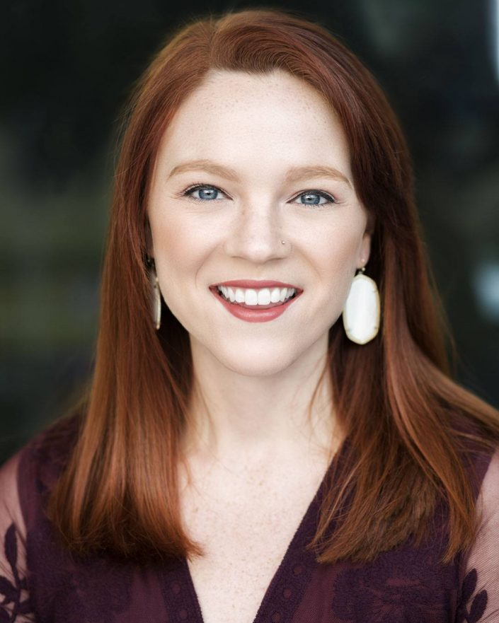 Headshot portrait of redhead woman smiling