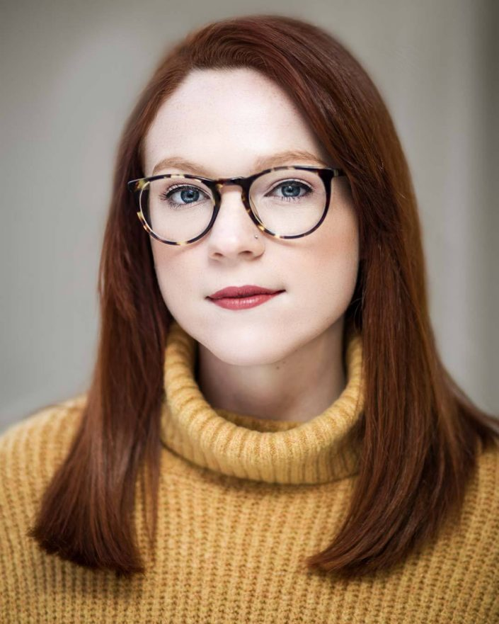 Headshot portrait of woman in yellow sweater with glasses