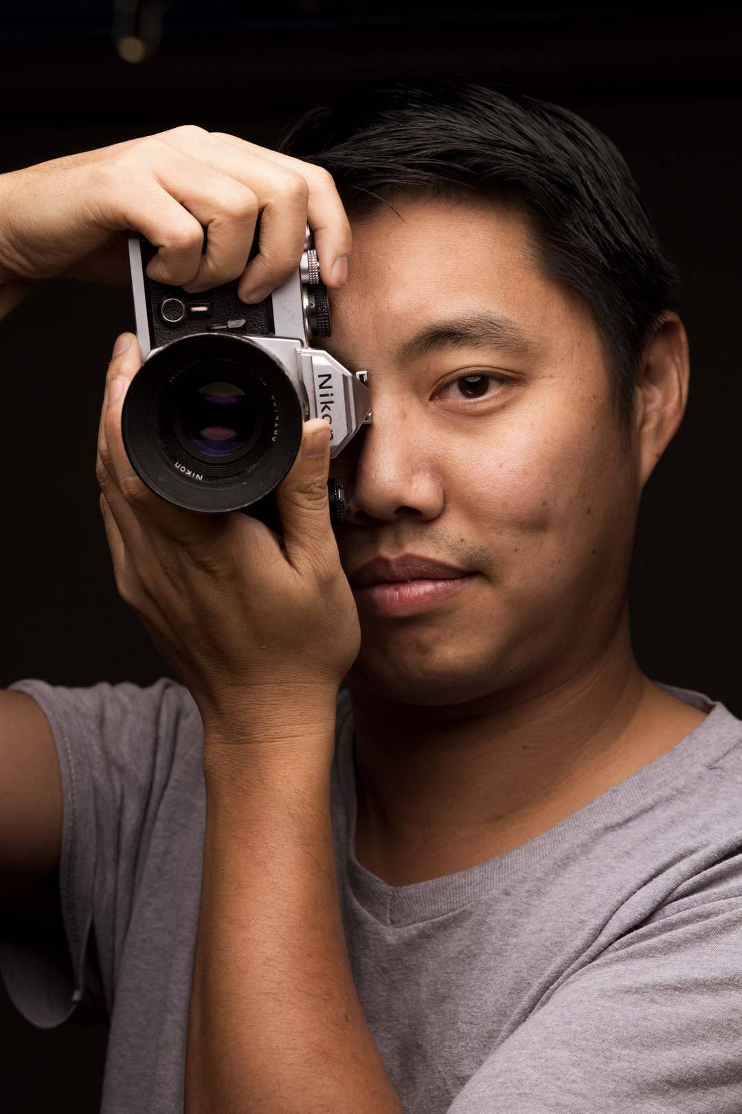 Close portrait of man holding camera