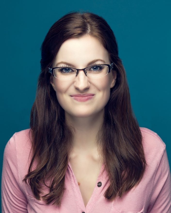 Headshot portrait of woman in pink top with glasses